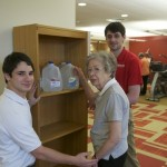 Sacred Heart students work with Irma Peopon, testing her ability to lift the full jugs. Photo Credit: Skip Pearlman