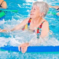 Woman doing water aerobics with noodle