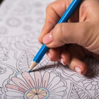 Girl paints a coloring book for adults with crayons