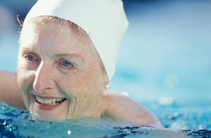 Senior woman swimming in pool, close-up of face