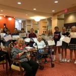 Greens Farm Academy and residents holding up placemats.