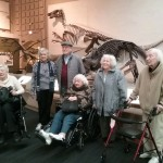 Assisted living residents of The Inn pose for a group picture with a prehistoric dinosaur
