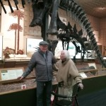Assisted Living residents from The Watermark at 3030 Park, Richard and Eugenie, in front a larger than life prehistoric skeleton of a dinosaur