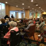 A group of independent living residents at The Watermark at 3030 Park in their main lounge listening to 2 talented musicians.