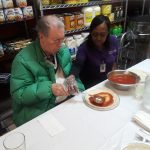 Gardens resident and caregiver, working together to create a delicious pizza.