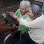 Our Gardens and Inn community residents at The Watermark at 3030 Park sharing a lovely moment with their new found friend at the Stamford Museum & Nature Center.